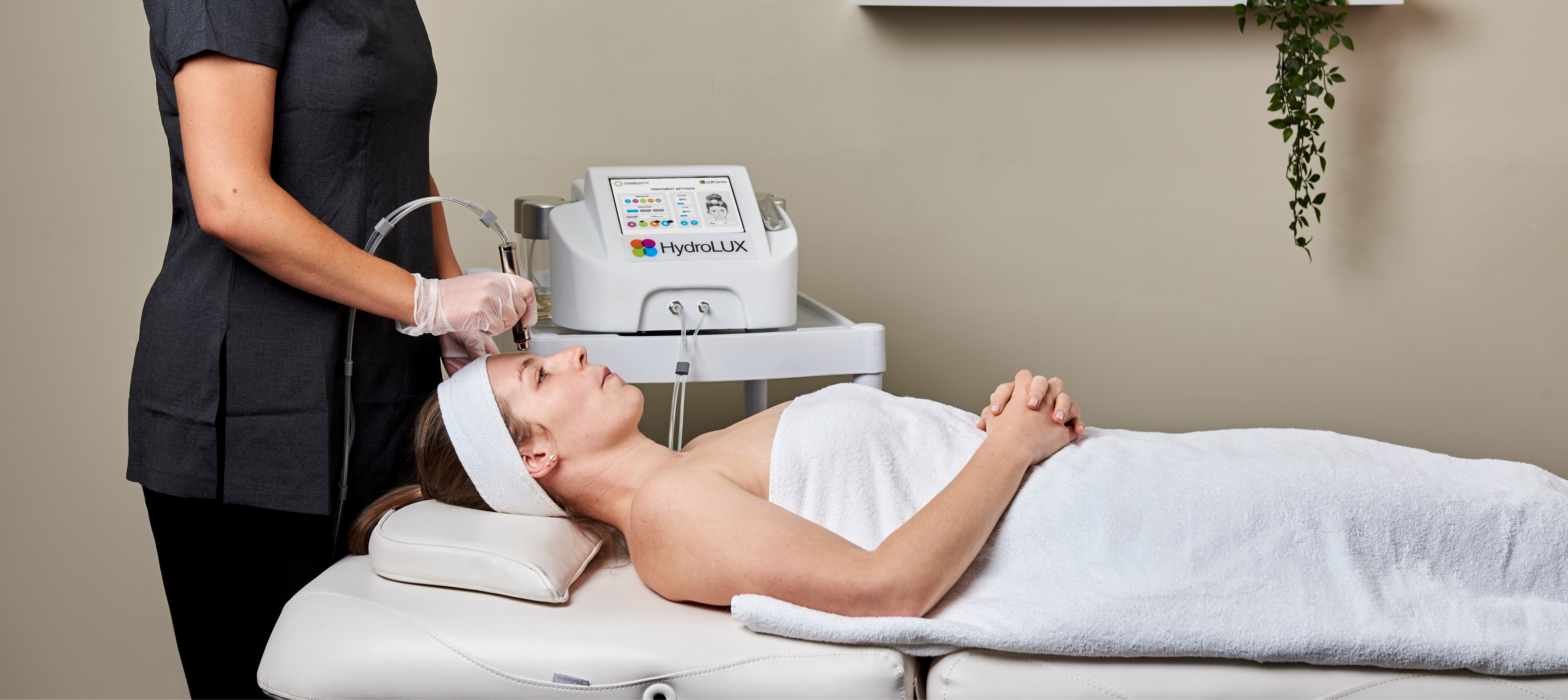 A skin consultant assessing a patient's skin with LED light therapy in Cardiff